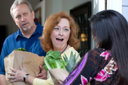 good samaritan: A look of surprise emotion is on the recipients faces as a charity relief worker brings bags of food and groceries to the hungry. Stock Photo
