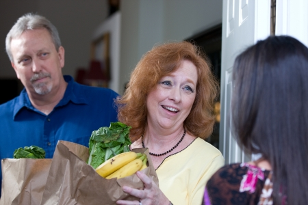 charitable: Woman delivers bags of food to the home of a down on their luck couple who have been laid off from their jobs.