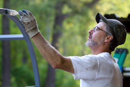 cartilla: Hombre maduro pinta herrajes con la brocha de aplicar el imprimador al metal.