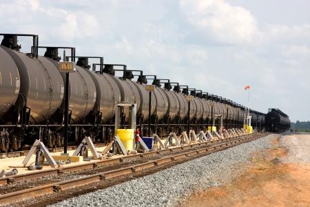 긴 유선의 유조선은 짐을 싣기를 기다리고있는 기차 트랙을 따라 내려갑니다. 에디토리얼