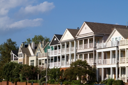 Multi-level high end executive townhomes with porches lines a street against a blue sky. Stock Photo
