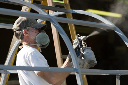 Construction worker spray paints while wearing respiratory safety equipment to protect himself from the fumes at a factory.