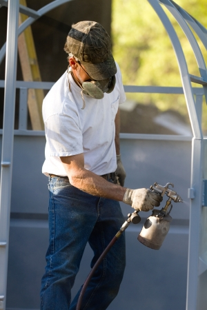 Construction steel worker uses a paint sprayer to apply a primer coat to metalwork. Imagens