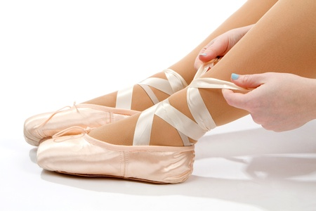 Female dancer ties on her pink ballet slippers with ribbons on a white background. photo