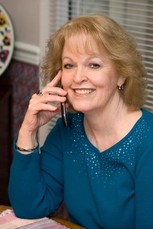 conversaciones: Mujer conversaciones jubilado mayor en su tel�fono celular en casa sentado en la mesa.