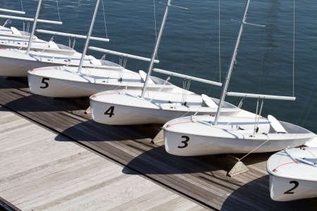 rentals: Small rental centerboard sailboats line the pier at a yacht club on the water.