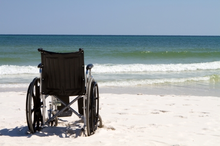 Empty wheelchair sits vacant on a beach of sand with ocean waves and surf in the background. Stock Photo