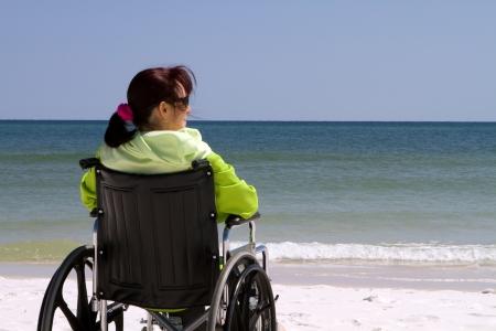 persona en silla de ruedas: Mujer con discapacidad se sienta desconectado en su silla de ruedas en la playa. Foto de archivo