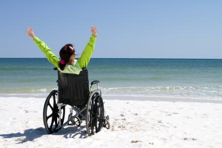 paraplegic: Vrouw met opgeheven armen viert haar prestatie en succes in de zon, zelfs met haar handicap in een rolstoel.