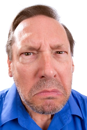 annoying: Face of angry senior adult man with Parkinsons disease as he stares with a threatening look.
