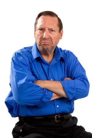 complaining: Grumpy moody senior man sits with his arms crossed and an unhappy expression on his face.