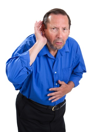 Senile senior adult male cups his hand to the ear because of a loss of hearing problem.
