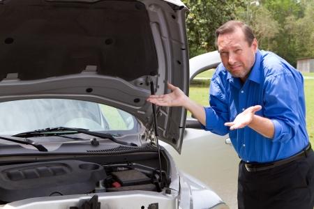 Senior man heeft hulp nodig en gebaren in frustratie over zijn auto die is gebroken en hoeven reparatiewerkzaamheden.