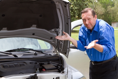 damaged vehicles: Senior man needs help and gestures in frustration about his car that is broken and needing repair work. Stock Photo