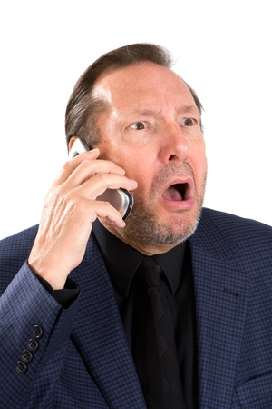 Upset elderly businessman talks on his cellphone with an emotional look on his face. Banco de Imagens