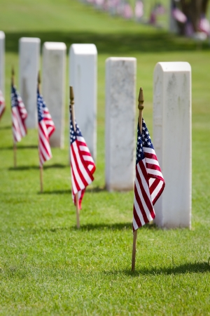 a memorial to fallen soldiers: American flags on gravesites commemorate Memorial Day at a United States national cemetery  Stock Photo