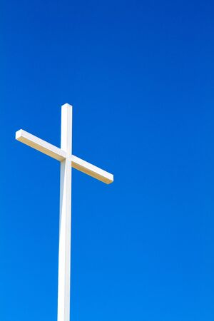 easter cross: White steel fabricated Christian cross stands out against a clear blue sky