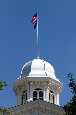 carson city: Nevada state capitol dome located in Carson City, NV against a blue sky background with flags flying on top
