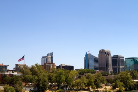 ca: Distant view of the city of Sacramento, California with skyscrapers rising above the treeline