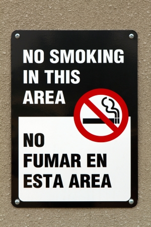 Bilingual no smoking sign with graphic and written in the English and Spanish languages is screwed to a wall