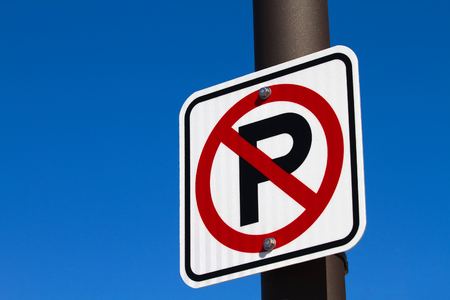 zoned: Sign showing a capital P with a red circle denoting a no parking area is attached to a pole against a blue sky