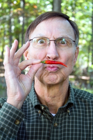 pungency: Senior adult holds a red chili pepper under his nose in a mustache position with a silly look on his face.