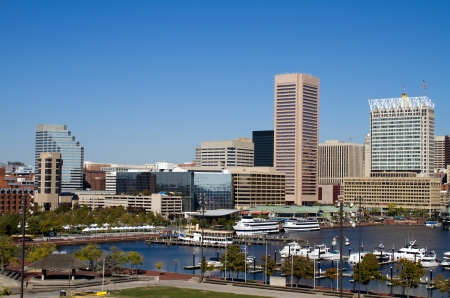 commercial district: Downtown Baltimore, Maryland city inner harbor skyline showing the marina, buildings and business on a clear sunny day