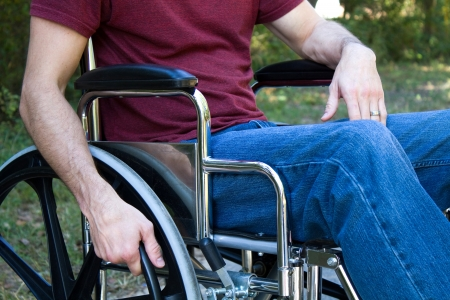 Man disabled by an accident sits in a wheelchair outside. Stock Photo