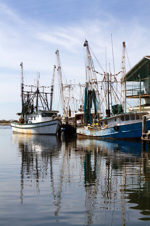 fishery: Two old rusty shrimp boats are docked at a pier with reflections in the water  Stock Photo