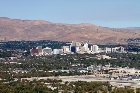 The city skyline of Reno, Nevada with the surrounding urban area and foothills in the distance