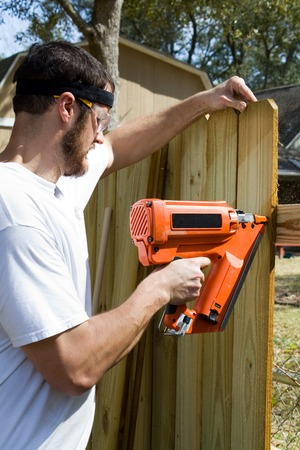 builds: Man wearing safety glasses uses a portable nail gun to attach wood pickets to the rail as he builds a privacy fence in the backyard.