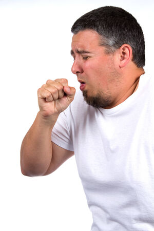 Sick adult male coughs into his fist.