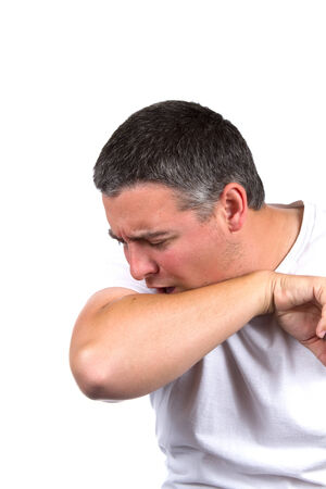 Sick adult male coughs inside his elbow to prevent the spread of germs.