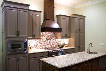 New modern luxury kitchen cabinets, with gas stove and granite countertops and high ceiling. photo
