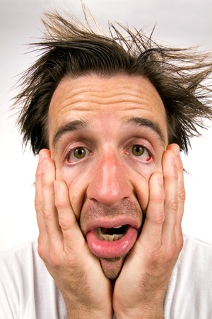 desperate face: Desperate man holding his face in hands appears in a miserable state of unhappiness. Stock Photo