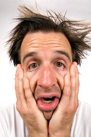 desperate: Hombre desesperado sosteniendo su cara entre las manos aparece en un estado miserable de infelicidad.