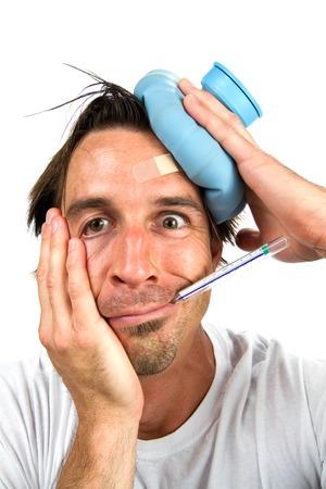 chorowity: Gorączkowe chory człowiek trzyma butelkę wody do głowy, podczas gdy on zajmuje jego temperatury z termometrem w ustach.