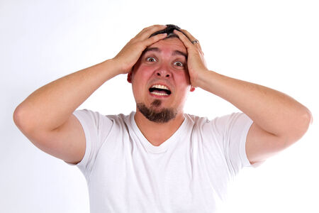 despondency: Stressed out man clutches his head as he is overwhelmed with emotion.
