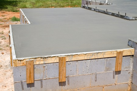 New construction of a freshly poured concrete slab floor on a residential home cures and hardens.