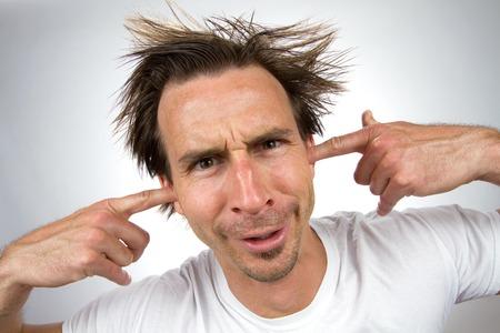 gestos de la cara: Desaliñado hombre de aspecto desagradable con una expresión facial tonta y pelo rebelde pone sus dedos en los oídos para que no se puede oír. Foto de archivo