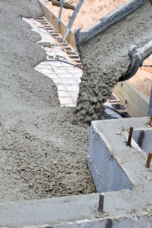 Wet cement pours down a concrete truck chute to fill a slab at a home building construction site.