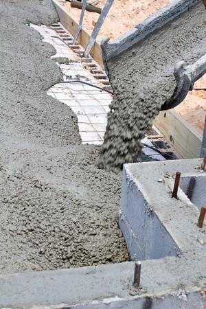 Wet cement pours down a concrete truck chute to fill a slab at a home building construction site. Reklamní fotografie - 30323573