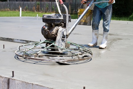 Construction worker uses a motorized power trowel to smooth and finish a concrete slab at a new home job site.