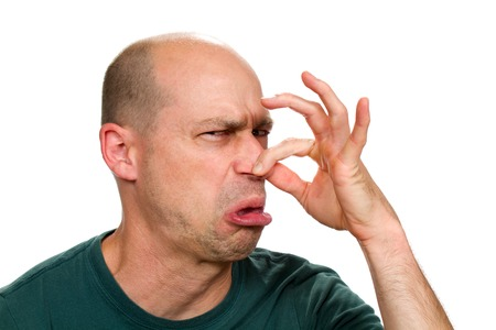 smells: Man smells something stinky and pinches his nose to stop the bad odor. Stock Photo