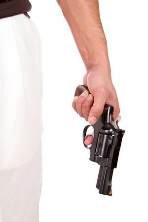 finger on trigger: Violent man holds a 357 magnum revolver at his side with his finger on the trigger.