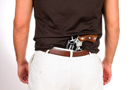 concealed: Man with revolver has the weapon concealed behind his back in his pants.