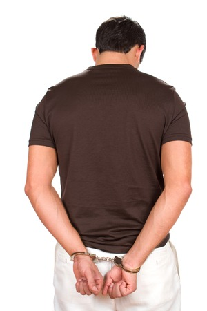 Arrested criminal stands with his hands handcuffed behind his back. photo