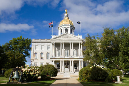 surrounding: The state house capital building of New Hampshire is located in the city of Concord, NH, USA with surrounding grounds.