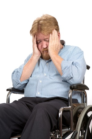 Worried and depressed disabled man in a wheelchair holds his head in his hands.