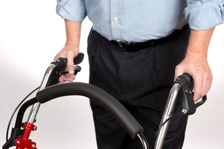 Elderly disabled man is using a walker to keep from falling and to give him stability as he walks alone for independent living.